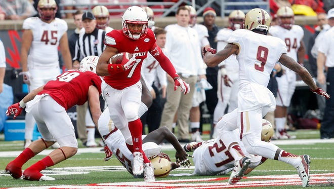Louisville's Reggie Bonnafon gets past a couple of defenders and gets ready to make contact with Boston College's John Johnson. Oct. 24 2015