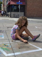 Lucy, 8-year-old daughter of Anne Malcore of Green Bay, draws a cat with chalk in a picture frame on the sidewalk outside The Children's Museum of Green Bay on North Washington Street in downtown Green Bay during Artstreet on Sunday, Aug. 28, 2016. Malcore's 2-year-old son, Sid, drew a dog in the same square, which was part of the HSHS St. Vincent Children's Hospital Children's Area at the 35th annual festival.