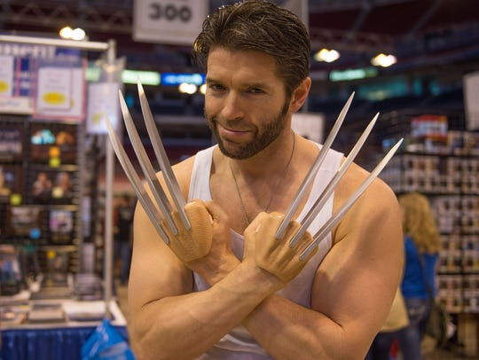 An actor posing as Wolverine with his signature claws.