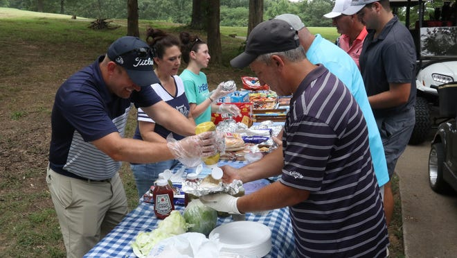 Greenwood Boys Golf Coach Tyler Woods, from left, Tara Carney and Tara Gamble serves hamburgers during the Greenwood Golf Team Booster 3-Person Scramble, Saturday, June 27, 2020, at Vache Grasse Country Club. Woods said that 38 teams competed in the fundraiser that multiple flight, prize payouts, closest to the pin and longest drive winners.