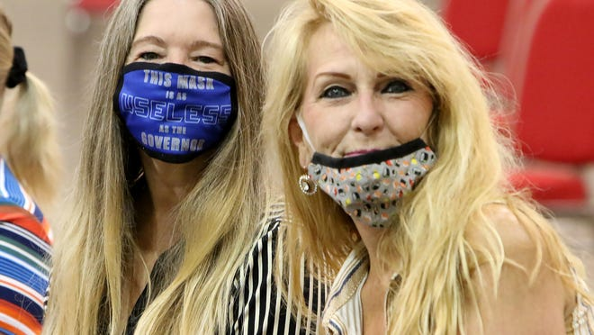 """Lisa Bohanan-Shoffey, left, and her sister, Donna Bohanan, show where they stand on the """"mandatory"""" mask ordinance with a personalized mask, worn Saturday, July 11, 2020, to the Fort Smith Board of Directors study session at the Fort Smith Convention Center."""