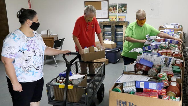 Miriam Cameron, from left, Danielle Carty and Mulberry Pantry Director, Alice Mainer load USDA commodities for distribution, Tuesday, July 21, 2020, at the Mulberry Community Food Bank. The Commodity Supplemental Food Program provides supplementary USDA food stuffs to those in need and is one of 15 federally funded nutrition assistance programs offered through the federal government.
