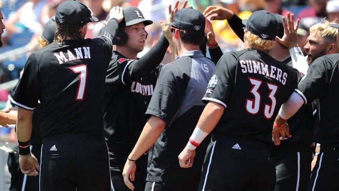 U of L's Drew Ellis (10) was greeted by teammates after being knocked in by Colin Lyman (35) against Texas A&M during Game 3 of the College World Series in Omaha, Neb.  June 18, 2017