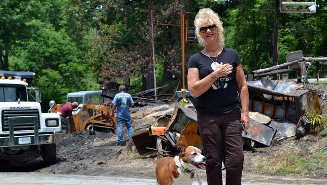 Mona Johnson stands with her dog Cici on Saturday in front of the remains of Bob's Place, a bar she and her mother have run for several decades that burned down on May 20.
