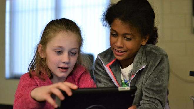 Carolina Comstock, left, and Erin Lyda, both eight years old, work on an iPad together during Sandy Bradshaw's Project Lead The Way Launch class at Midway Elementary on Wednesday, Nov. 1.