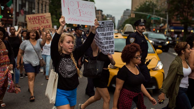 Protesters shouts slogans and carry placards as they march form Manhattan to Brooklyn in New York, July 8, 2016.