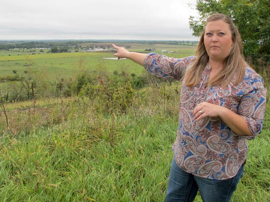 In this Tuesday, Sept. 26, 2017 photo, Shannon Reischman, points to the site of a proposed Tyson Foods Inc. chicken-processing plant from a hill behind her in-laws farmhouse outside Tonganoxie, Kan. She and other residents mobilized against the project, and the company is now looking elsewhere.