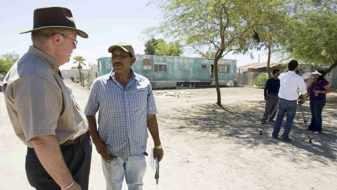 Riverside County Supervisor John Benoit, left, speaks to resident Manuel Marroqui during a tour of the blighted Duroville mobile home park by county officials in 2012.