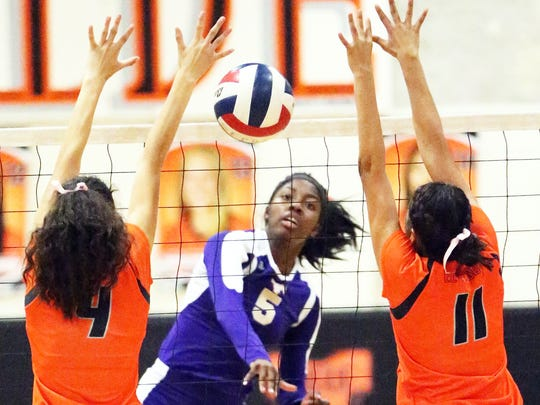 Arielle Mack, 5, of Burges places the ball between