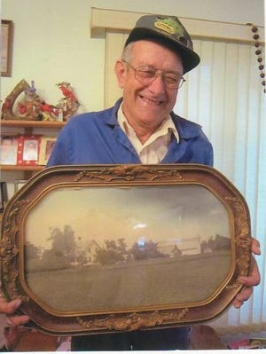 Elmer Maciejewski holds a picture of his farm taken in the 1930s or 1940s.