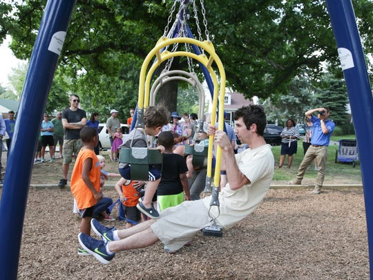 "Andy Mundell and his son River try out the newly installed Expression Swing after a dedication ceremony and ribbon cutting celebrating the play legacy of The ""founding father of play studies"", Bernie ""Blue"" DeKoven at Ellenberger Park in Indianapolis on Thursday, June 29, 2017. Game Time, a Playground equipment supplier donated the Expression Swing which was installed thanks to a fundraising effort by Indy Parks and Recreation and the DeKoven family."