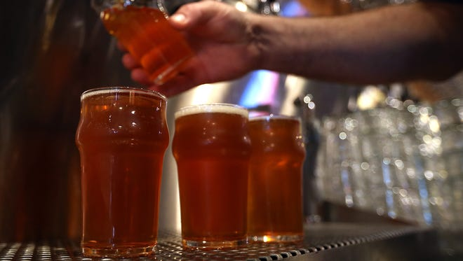 A Russian River Brewing Company bartender pours a glass of the newly released Pliny the Younger triple IPA beer on February 7, 2014 in Santa Rosa, California.