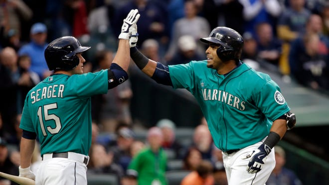 Seattle Mariners' Nelson Cruz, right, is congratulated by Kyle Seager after his home run against the Minnesota Twins in the second inning of a baseball game Friday, April 24, 2015, in Seattle.