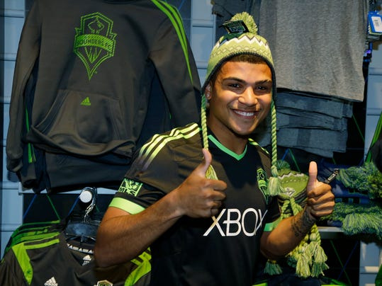 """FILE - In this March 3, 2014 file photo, Seattle Sounders' DeAndre Yedlin adds a hat to his modeling of the MLS soccer team's new """"third kit"""" uniform at the CenturyLink Field Pro Shop in Seattle. Yedlin is back with the  Sounders but far more known than when he left for U.S. national team camp nearly two months ago. After an impressive performance in the World Cup, the question now is how long can Seattle hold on to its budding homegrown star?  (AP Photo/Ted S. Warren, File)"""