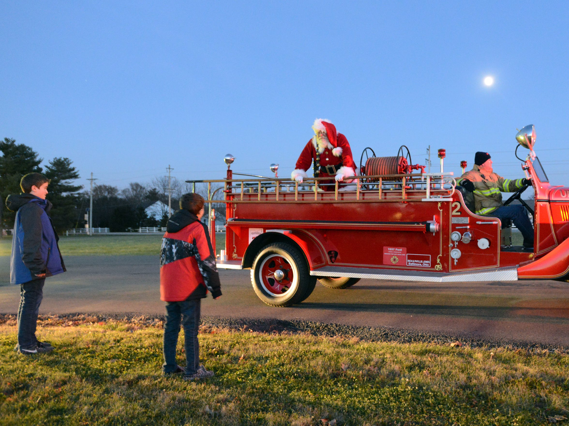 Tim Etienne talks to two children as he stands in the back of an antique fire truck