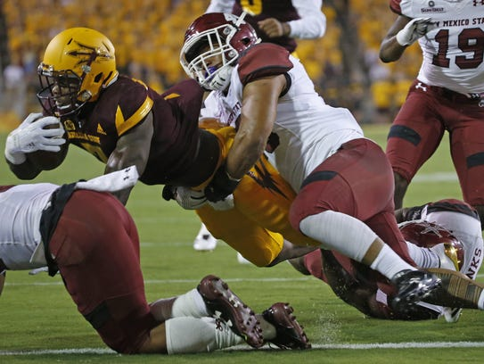 ASU's Kalen Ballage (7) drags New Mexico State defenders