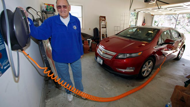 """James Brazell poses with a charging unit for his Chevy Volt electric car at his home in Asheville, N.C. Brazell plugs the car in after short trips. """"Pretty much I top it up every time I bring it into the garage,"""" he said."""