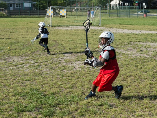 A Doverdale Lacrosse player practices a passing drill.