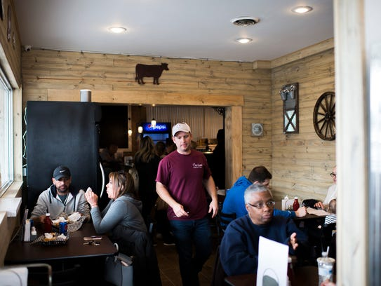 Owner Ryan Briggs checks on customers at Outlaw's Burger