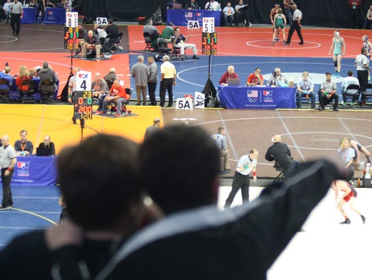 Two young fans watch first-round state wrestling action