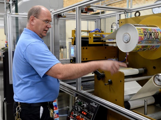 Kevin Mickelson, the supervisor of the Print and Sign shop at Deer Lodge State Prison, describes the process of applying the license plate face to the aluminum backing in the license plate shop recently.