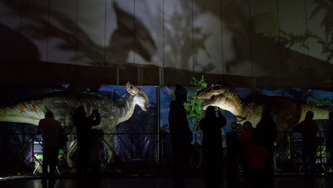 Attendees look at a Olorotitan and Ablertosaurus dinosaur on display during the Jurassic Quest event at the Kentucky Convention Center Saturday afternoon. January 17, 2015. January 17, 2015.