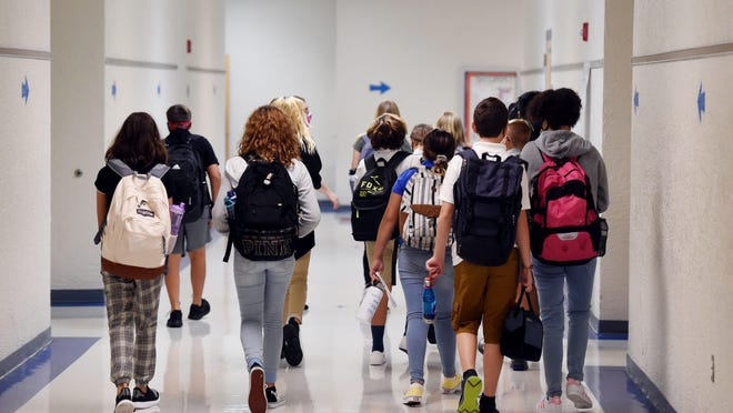 Students make their way down the hall to the cafeteria on Tuesday, Aug. 11, 2020, on the first day of school at Stuart Middle School in Stuart. All students and faculty must wear masks and undergo temperature checks.
