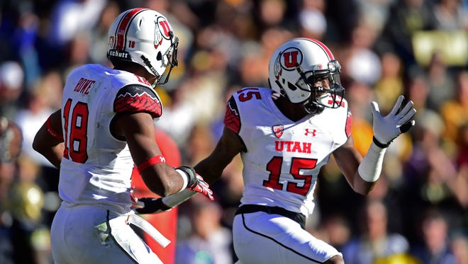 Utah Utes defensive back Dominique Hatfield (15) celebrates with Utah Utes defensive back Eric Rowe (18) after returning an interception for the go-ahead touchdown in the fourth quarter against the Colorado Buffaloes at Folsom Field.