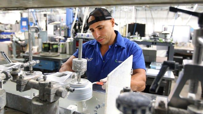 Otto Solano works at a polishing station at Optimax in Ontario, Wayne County.