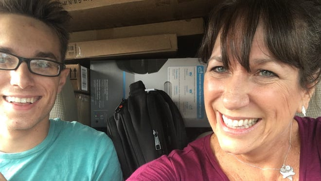 Karina and her son Sawyer in the tightly packed car with his belongings on dorm move-in day in 2017.