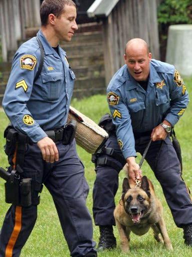"Detective Cpl. Walter Rawa, left, plays the part of the ""bad guy"" as Detective Cpl Frank Perez gives commands to his K-9 dog Zander, during a demonstration. Morris County School of Technology students visit Idlewild Pool for a swim, picnic and recognition by Idlewild Pool and the Morris CountySheriff's Office K-9 unit. The students constructed a deck and dog houses as well as a small bathhouse and shed at the pool, June 10, 2014. Morris Plains NJ. photo by Kathy Johnson  MOR 0611 MCST Students K9s"