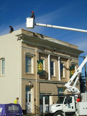 Town of Windsor employees lift cinder blocks to the roof of the Art and Heritage Center so that Christmas lights can be placed on the roof line in this file photo.