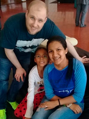 ADDS NAME OF DAUGHTER - In this image provided by the Holt family, Joshua Holt poses for a photo with his wife Thamara and her daughter Marian Leal, at the airport in Caracas, Venezuela, Saturday, May 26, 2018.  Jailed in Venezuela on weapons charges nearly two years ago, Holt was released Saturday after a U.S. senator pressed for his freedom in a surprise meeting with President Nicolas Maduro. Holt and his wife, who also jailed, were reunited with her daughter from a previous relationship at Caracas' airport where the three boarded a chartered flight to Washington. (Holt family photo via AP)