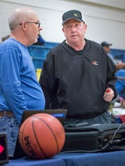 Tournament directors Arnold Gamber, left, and Chip Boes chat during halftime of the Gulf Breeze vs. Letcher County Central (Kentucky) girls basketball game in the Innisfree Hotels Pensacola Beach basketball tournament at Gulf Breeze High School on Thursday, December 28, 2017.