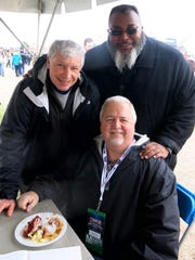 Times Sports Reporter Jimmy Watson (clockwise from seated), Preston Friedley, state Rep. Cedric Glover at Glover's barbecue booth at Walk-On's Independence Bowl.