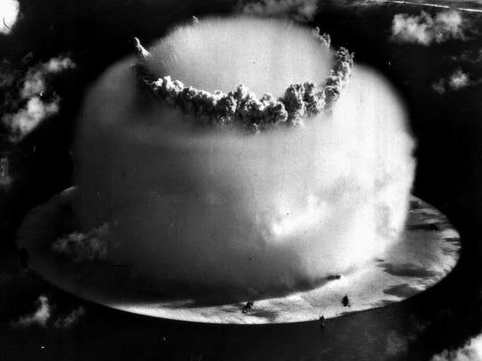 A huge mushroom cloud rises above Bikini atoll in the