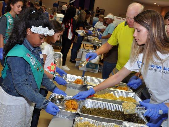 Volunteer Aspyn Dorsett scoops green beans into a family-sized