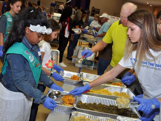 Volunteer Aspyn Dorsett scoops green beans into a family-sized meal held by Girl Scout Abby Tapia during Feeding of the 5,000 prep Nov. 23 at Lamb of God Church.