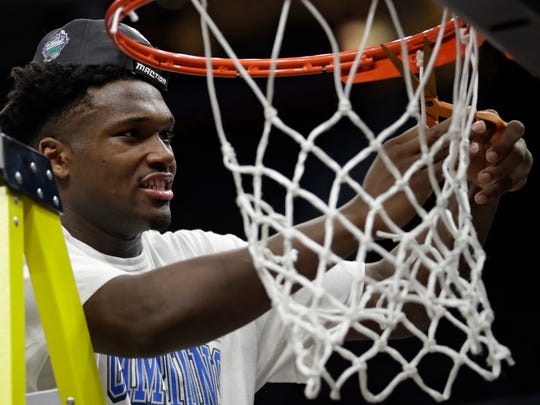 Buffalo's Nick Perkins cuts the net after Buffalo defeated Toledo 76-66 during an NCAA college basketball championship game of the Mid-American Conference tournament, Saturday, March 10, 2018, in Cleveland.