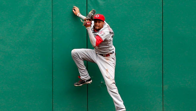 Cincinnati Reds center fielder Billy Hamilton comes off the center field wall with a catch on a deep fly ball hit by Pittsburgh Pirates' Travis Snider during the ninth inning of a baseball game in Pittsburgh, June 19, 2014