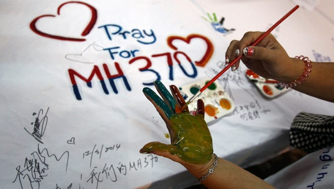 A woman paints her palm before creating a hand print on a sign Monday in Kuala Lumpur, Malaysia.