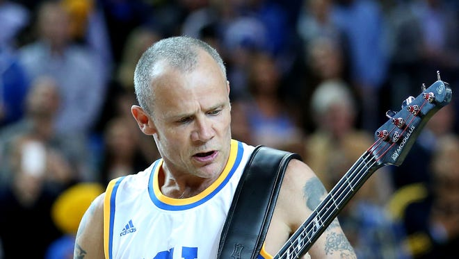 Bassist Flea of the Red Hot Chili Peppers performs the national anthem before the game between the Arizona Wildcats and the UCLA Bruins on Jan. 9 in Los Angeles.