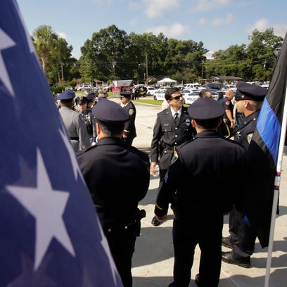 Law enforcement personnel gather near flags before
