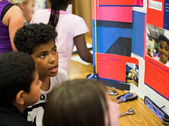 Omar Rodriguez talks to students about the career he chose — carpenter — as fifth grade students at Northwest Elementary School, Lebanon, presented their career fair projects on Thursday, May 26, 2016. Students researched careers they were interested in and made posters detailing requirements for the careers, salaries and why they chose the career.