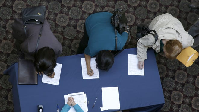 Job seekers register before meeting prospective employers at a career fair in Dallas on Tuesday.