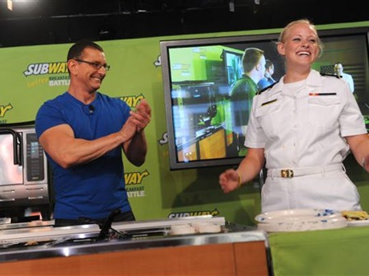 Celebrity chef Robert Irvine, left, congratulates Fleet Week sailor Emily Kreyenhagen after winning a round in the Subway 'Better Breakfast Battle.'