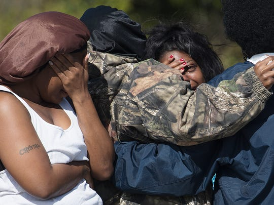 Family members of Jontavious Thomas react at the scene of his death off of Adeline Avenue in Lehigh Acres. Members of the Lee County Sheriff's Office are considering his death a homicide and are investigating. A large number family members arrived to get information into his death.