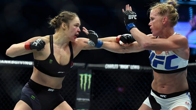 Ronda Rousey, left, and Holly Holm fight during their UFC 193 bantamweight title bout in Melbourne, Australia, Sunday, Nov. 15, 2015. Holm pulled off a stunning upset victory over Rousey in the fight, knocking out the women's bantamweight champion in the second round with a powerful kick to the head Sunday.