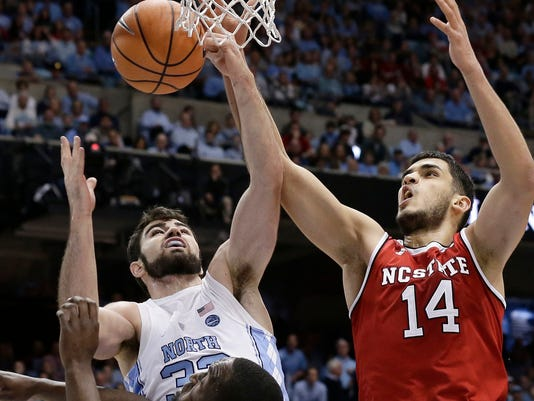 FILE - In this Jan. 27, 2018, file photo, North Carolina's Luke Maye, left, and North Carolina State's Omer Yurtseven (14) battle for a rebound during the first half of an NCAA college basketball game in Chapel Hill, N.C. Maye is leading the No. 21 Tar Heels in scoring (18.3) and rebounding (10.3) entering Thursday's rivalry game with No. 9 Duke. (AP Photo/Gerry Broome, File)