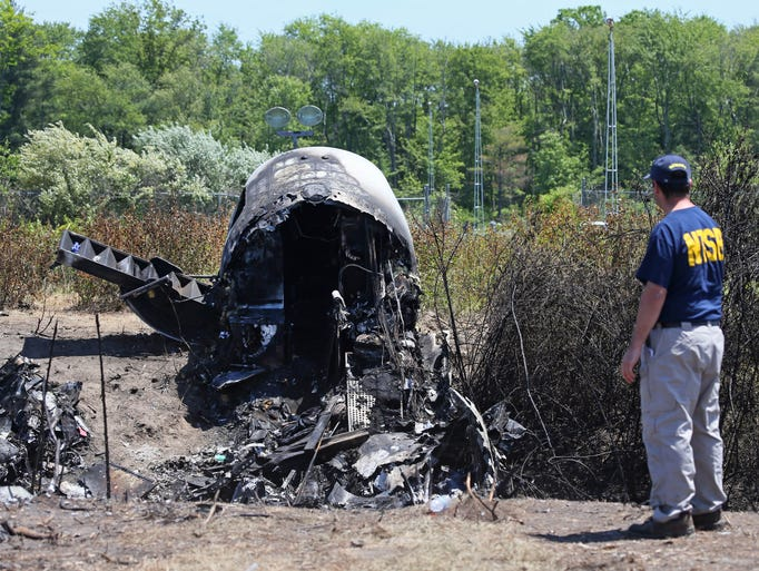 An NTSB official looks at wreckage at the scene Monday, June 2, 2014, in Bedford, Mass., where a plane plunged down an embankment and erupted in flames during a takeoff attempt at Hanscom Field Saturday night. Lewis Katz, co-owner of the Philadelphia Inquirer newspaper, and six other people died in the crash. (AP Photo/Boston Herald, Mark Garfinkel, Pool)